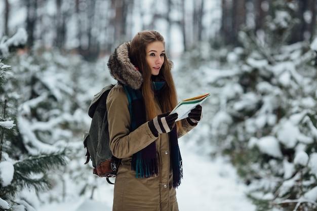 旅行者の女性は冬の雪の森の中で彼女の手に地図を持っています。旅行コンセプト