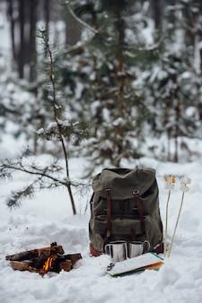 Зимний кемпинг. костер с рюкзаком для путешествий, карта, две кружки и зефир на снегу