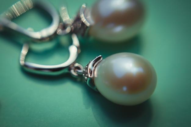 ミント紙に横たわる輝く真珠のイヤリングの拡大写真