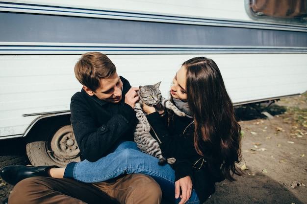 幸せな恋人は灰色の猫と地面に座っている恋人の美しいカップルが猫と遊んでいます。