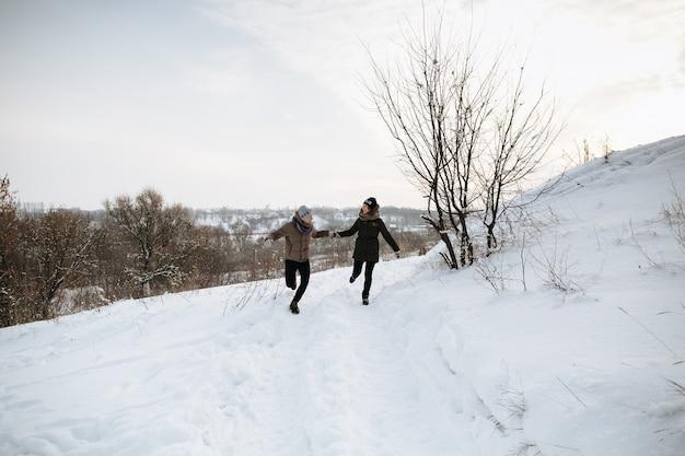 幸せな夫婦は雪の冬の日に手を握って走ります。冬の愛。ラブストーリー。