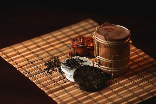 暗い背景に仏の彫像と謝る茶。伝統的な中国のお茶。
