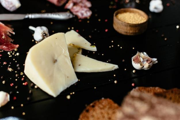 黒い木製のテーブルにフェスタシカミとおいしいチーズ