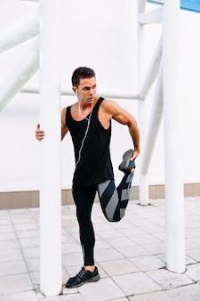 Молодой привлекательный спортсмен в гарнитуру, занимающийся спортом растяжения упражнения во время тренировки
