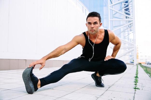 Полная длина вид мужчины-спортсмен делает упражнения на растяжку для тела, слушая музыку