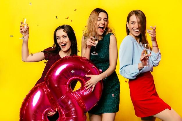 シャンパンのワイングラスを持つ魅力的な笑顔の若い女性