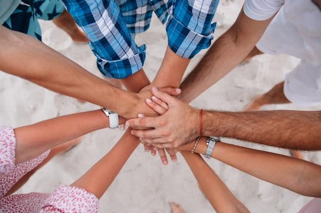 一緒に手を結ぶ人々、手を一緒にしている友人のグループ。