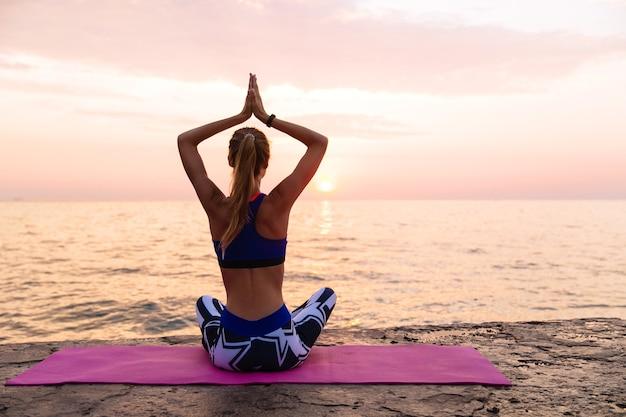 日の出のヨガ。釣り好きな女性、ヨガを練習し、蓮の姿勢で桟橋に座っている