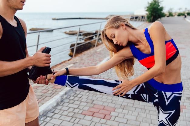 彼女のボーイフレンドが彼女を助けている間、ストレッチ練習をしている若いかわいい女の子の側面図
