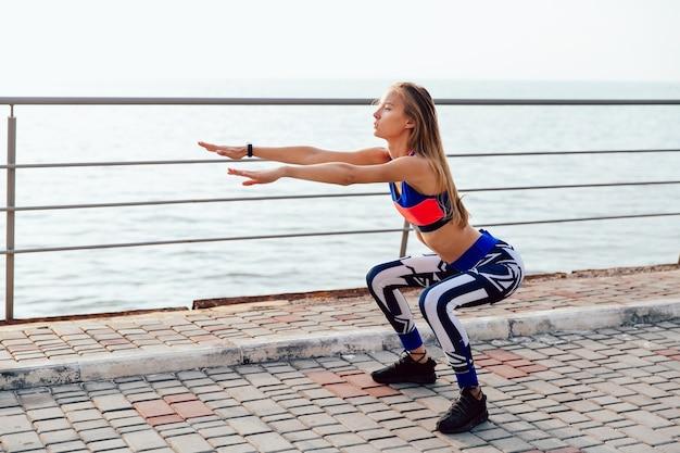海岸近くの岸辺で運動中にスクワットをするブロンドの美しい女の子