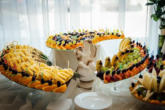 Отрезанные фрукты лежат на изогнутых лотках