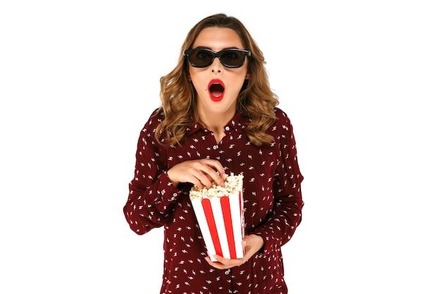 Молодая девушка в стерео очки, проведение попкорн и создает удивление