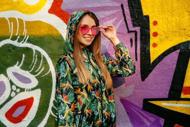 赤い眼鏡やフードで美しい女の子の通りの写真。緑色のカラフルなジャケットで服を着た
