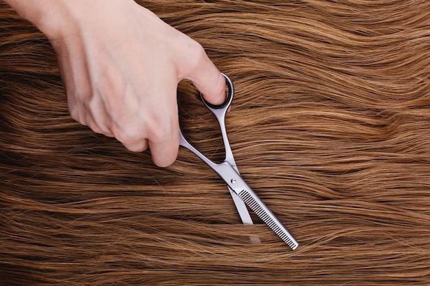 Женщина режет каштановые волосы стальными ножницами