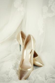 Элегантная золотая обувь стоит на кружевной свадебной вуалью