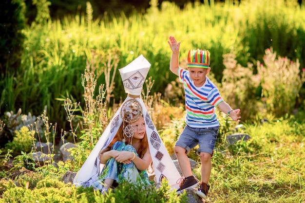 Дети играют как американские аборигены на зеленой траве в поле