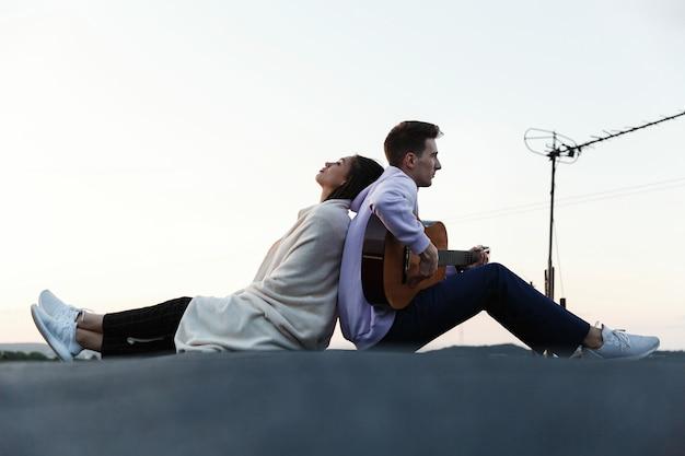 Человек играет на гитаре, пока его женщина наклоняется к нему нежно на крыше