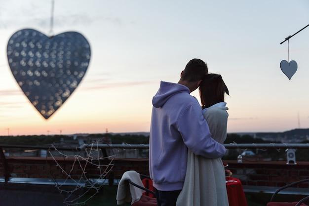 男の子と女の子は、夜の光線の光の中で屋根の上に立つ互いの優しい抱擁