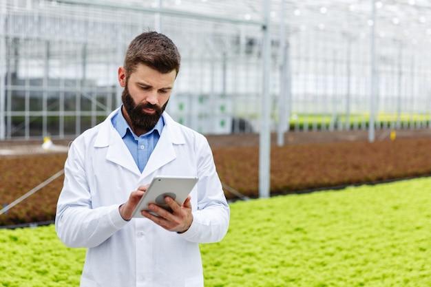 ひげをつけた男性研究者は、温室に立っている錠剤を使って植物を研究する