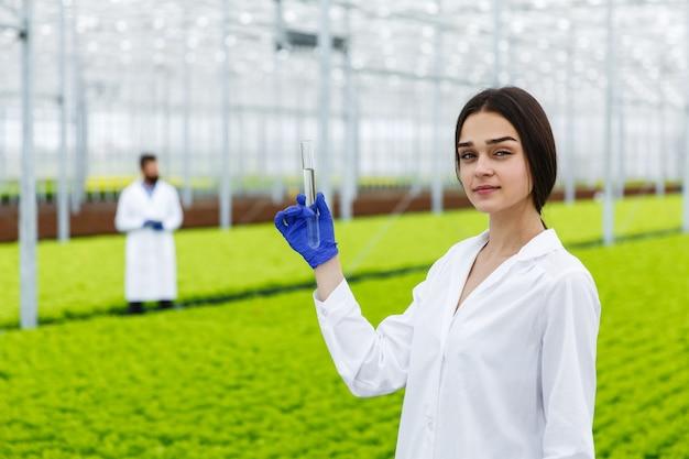 女性の研究者は、温室内の植物の前にサンプルが立っているガラス管を保持しています