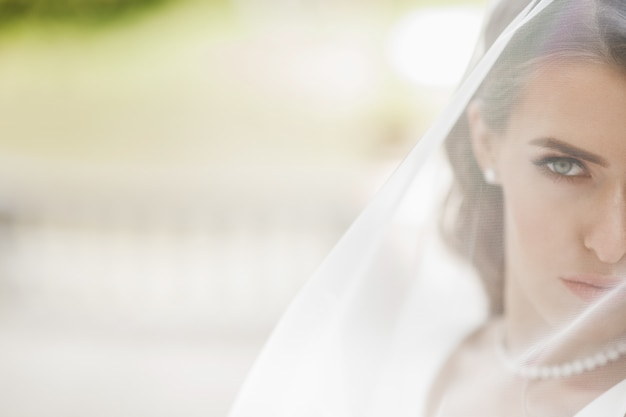 外のベールの下でポーズを取っている美しい花嫁の写真