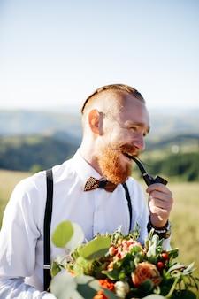 笑顔の新郎は、丘の上に立っている間パイプを吸う