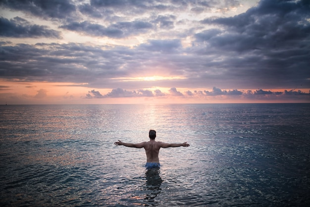 人は夕日に面した海水に立っている