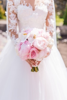リッチドレスの花嫁は、蘭と牡丹のピンクの結婚式の花束を保持しています