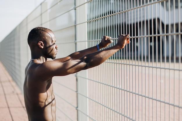 ハンサムなアフリカ系アメリカ人の男性は、外に出る前にストレッチをします