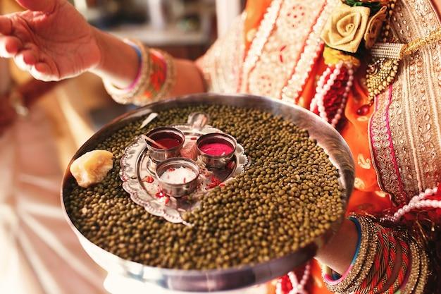 Индийская женщина несет тарелку с куркумой и специями