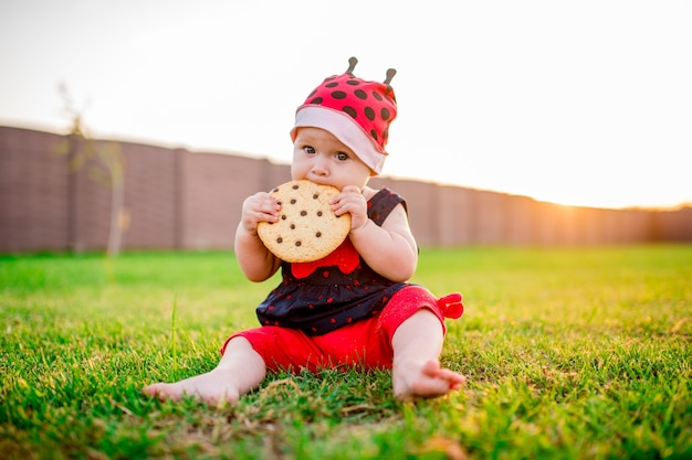 Маленькая девочка-девочка с большим шоколадным печеньем сидит на заднем дворе