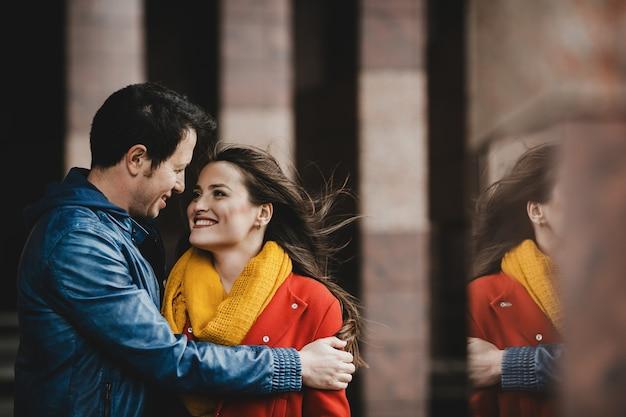 Прекрасная пара в любви, обнимающая возле стены