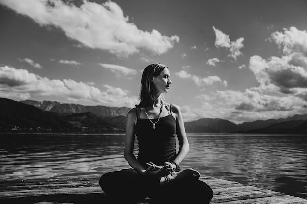 黒の服の美しい妊娠中の女性は、湖の上の木の橋に座っている