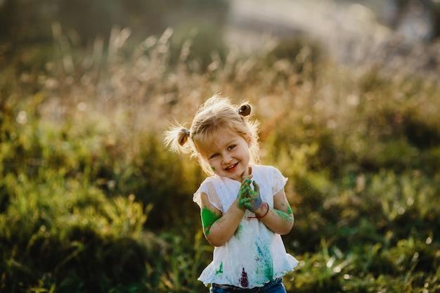 Очаровательная девочка с белой рубашкой, покрытой разными красками