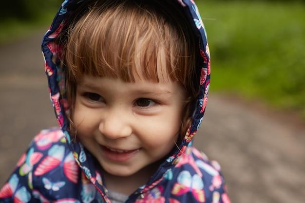 雨のコートの面白い少女は、緑の公園に立っている