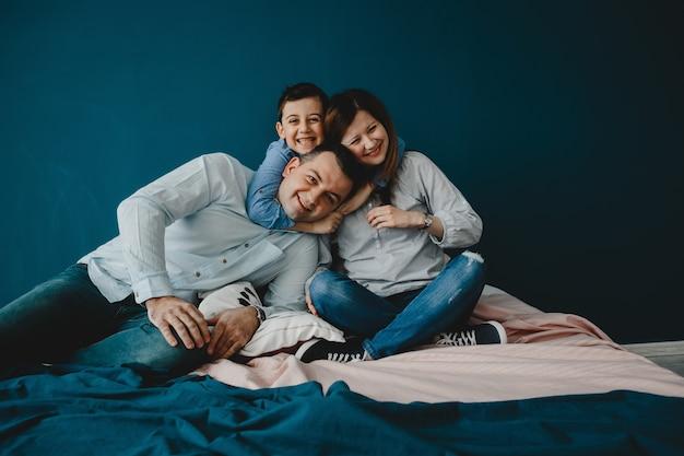 若い両親が息子とベッドに横たわっている