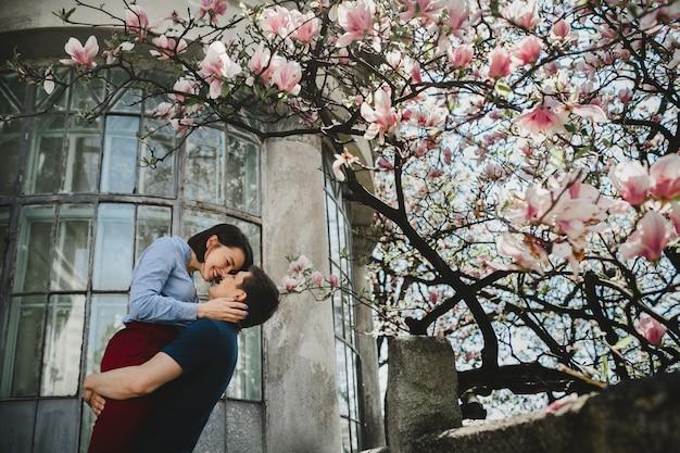素敵な若いカップルは、外に咲く木の下に立ってお互いに優しい抱擁