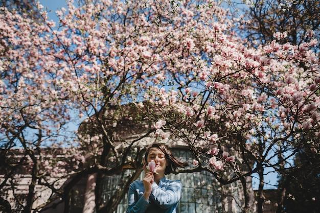 咲くピンクの木の下に立っている女性を下から見てください