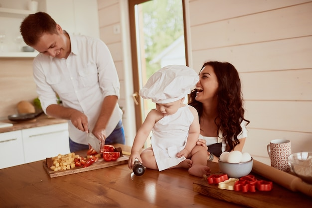 キッチンに座っている母、父、息子