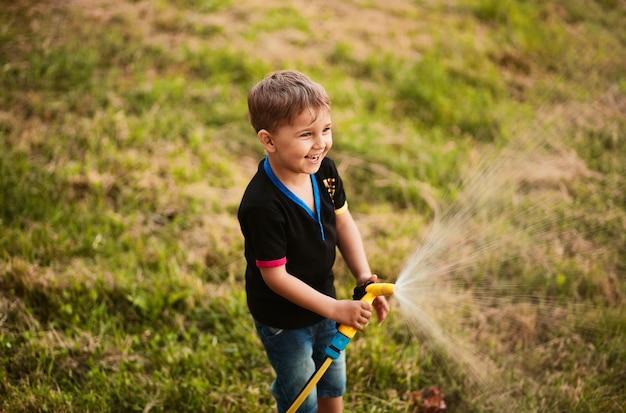魅力的な少年は裏庭の緑の草に水を吹きます