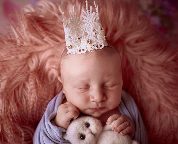 王冠を持つ小さな赤ん坊はバスケットに横たわっています