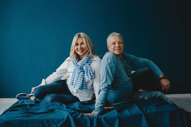 お父さんと彼の大人の娘が一緒に青いベッドに座って