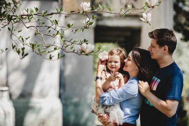小さな娘と幸せな若い両親は、ピンクの木の外に咲く下に立つ