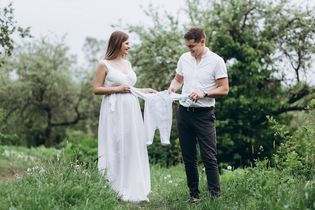 赤ん坊の服を着て、路地に沿って歩く妻と夫