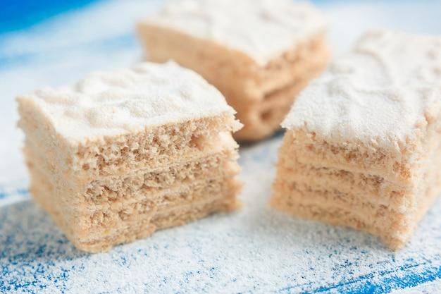 Пастила кусочки на фоне синего дерева, покрытые сахарной пудрой, вид сбоку