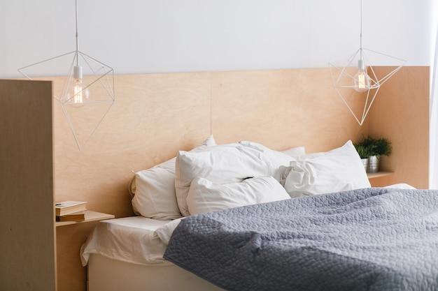 ロフト内装の木製ベッドヘッドを備えた黒と白のベッド、幾何学的なライト