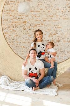 部屋の空のレンガの壁の近くに幸せな家族の父親、母親と子供の息子。