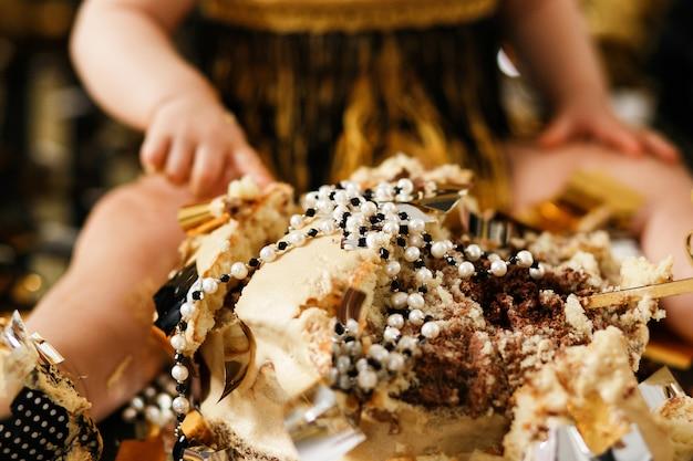 真珠のジュエリーで砕いたケーキのクローズアップショット。最初のベビーガールの誕生日パーティー