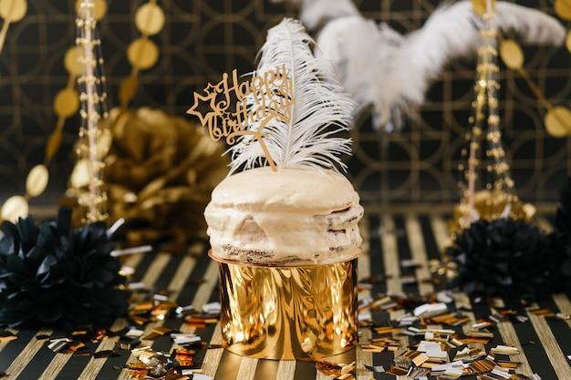 ゴールデンと黒のインテリアの様々な風船と誕生日パーティーのケーキ。