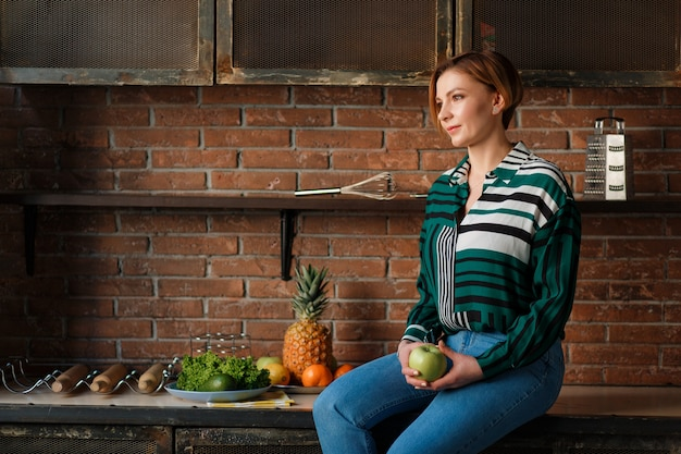 キッチンテーブルに座っている間、リンゴを持っているかわいい女性の肖像画。